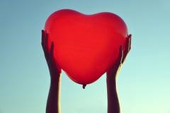 Χέρια που κρατούν το κόκκινο μπαλόνι με μορφή της καρδιάς Στοκ Φωτογραφία