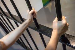 Χέρια που κρατούν το μαύρο φραγμό μετάλλων με την πίεση στοκ εικόνα με δικαίωμα ελεύθερης χρήσης