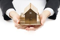 Χέρια που κρατούν το μικρό πρότυπο του σπιτιού κτήμα έννοιας πραγματικό Στοκ Φωτογραφίες