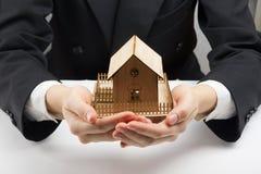 Χέρια που κρατούν το μικρό πρότυπο του σπιτιού κτήμα έννοιας πραγματικό Στοκ Εικόνα