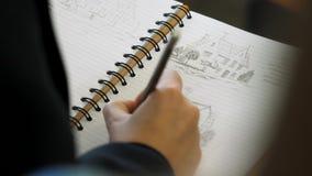 Χέρια που κρατούν το μολύβι που γράφει ή που σύρει σε ένα σημειωματάριο Ενήλικος χρωματισμός με τα μαλακά μολύβια ακρών Θηλυκό σχ απόθεμα βίντεο