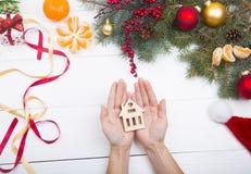 Χέρια που κρατούν το ξύλινο σπίτι στο υπόβαθρο διακοσμήσεων Χριστουγέννων Στοκ Εικόνα