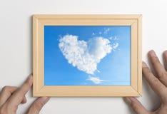 Χέρια που κρατούν το πλαίσιο εικόνων με το σύννεφο καρδιών Στοκ Εικόνα