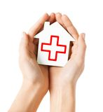 Χέρια που κρατούν το σπίτι εγγράφου με τον Ερυθρό Σταυρό Στοκ Εικόνες