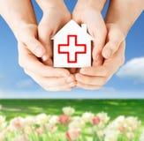 Χέρια που κρατούν το σπίτι εγγράφου με τον Ερυθρό Σταυρό Στοκ Φωτογραφίες