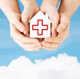 Χέρια που κρατούν το σπίτι εγγράφου με τον Ερυθρό Σταυρό Στοκ φωτογραφία με δικαίωμα ελεύθερης χρήσης