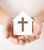 Χέρια που κρατούν το σπίτι εγγράφου με το διαγώνιο σύμβολο στοκ εικόνα με δικαίωμα ελεύθερης χρήσης