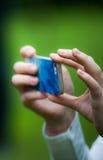 Χέρια που κρατούν το smartphone και που παίρνουν τους πυροβολισμούς Στοκ Φωτογραφία