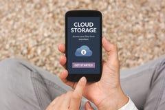 Χέρια που κρατούν το smartphone με app αποθήκευσης σύννεφων την έννοια στους βράχους σε λόφο Στοκ εικόνα με δικαίωμα ελεύθερης χρήσης