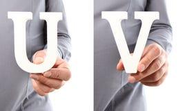 Χέρια που κρατούν το U και το Β επιστολών από το αλφάβητο που απομονώνεται σε ένα άσπρο β Στοκ φωτογραφίες με δικαίωμα ελεύθερης χρήσης