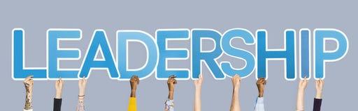 Χέρια που κρατούν ψηλά τις μπλε επιστολές που διαμορφώνουν την ηγεσία λέξης στοκ φωτογραφία