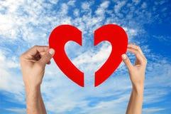 Χέρια που κρατούν δύο μισό της μορφής καρδιών με το μπλε ουρανό Στοκ εικόνες με δικαίωμα ελεύθερης χρήσης