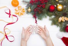 Χέρια που κρατούν snowflake στο υπόβαθρο διακοσμήσεων Χριστουγέννων Στοκ Φωτογραφίες