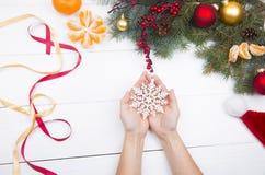 Χέρια που κρατούν snowflake στο υπόβαθρο διακοσμήσεων Χριστουγέννων Στοκ Εικόνες