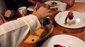 Χέρια που κόβονται από το εύγευστο μεγάλο κέικ σοκολάτας μαχαιριών στον πίνακα απόθεμα βίντεο