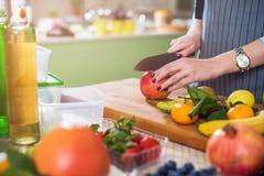 Χέρια που κόβουν ένα μήλο στον τεμαχίζοντας πίνακα Νέα γυναίκα που προετοιμάζει μια σαλάτα φρούτων στην κουζίνα της στοκ εικόνα