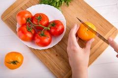 Χέρια που κόβουν την κίτρινη ντομάτα κοντά σε ένα άσπρο πιάτο με τις κόκκινες ντομάτες fersh σε έναν ξύλινο πίνακα Στοκ Εικόνα