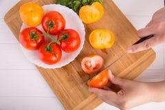 Χέρια που κόβουν την κίτρινη ντομάτα κοντά σε ένα άσπρο πιάτο με τις κόκκινες ντομάτες fersh Στοκ εικόνα με δικαίωμα ελεύθερης χρήσης