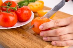 Χέρια που κόβουν την κίτρινη ντομάτα κοντά σε ένα άσπρο πιάτο με τις κόκκινες ντομάτες fersh Στοκ εικόνες με δικαίωμα ελεύθερης χρήσης