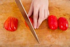 Χέρια που κόβουν την ντομάτα Στοκ Φωτογραφίες