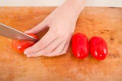 Χέρια που κόβουν την ντομάτα Στοκ Εικόνες