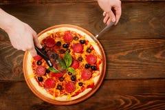 Χέρια που κόβουν την πίτσα στον ξύλινο πίνακα Στοκ Εικόνα