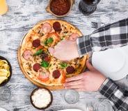 Χέρια που κόβουν την πίτσα στον πίνακα Στοκ Εικόνα