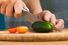 Χέρια που κόβουν το αγγούρι και την ντομάτα για τη σαλάτα Στοκ Φωτογραφίες