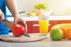 Χέρια που κόβουν το μήλο που κατασκευάζει το χυμό Στοκ εικόνες με δικαίωμα ελεύθερης χρήσης