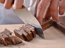χέρια που κόβουν το φραγμό σοκολάτας Στοκ εικόνες με δικαίωμα ελεύθερης χρήσης