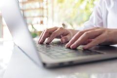 Χέρια που λειτουργούν και που δακτυλογραφούν στο πληκτρολόγιο lap-top στον πίνακα με το υπόβαθρο φύσης θαμπάδων Στοκ Εικόνες
