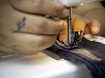 Χέρια που λειτουργούν στη ράβοντας μηχανή στοκ εικόνες