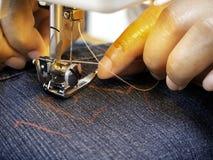 Χέρια που λειτουργούν στη ράβοντας μηχανή στοκ εικόνα