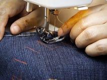 Χέρια που λειτουργούν στη ράβοντας μηχανή στοκ φωτογραφίες