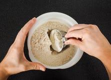 Χέρια που μετρούν το αλεύρι σίτου από ένα κύπελλο Στοκ Φωτογραφία