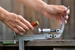 Χέρια που ξαναφορτώνουν την κασέτα από το κοχύλι κυνηγετικών όπλων reloader Στοκ Φωτογραφία
