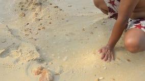 Χέρια που παίζουν με την άμμο στην παραλία απόθεμα βίντεο