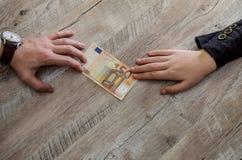 Χέρια που παίρνουν και που δίνουν τα ευρο- τραπεζογραμμάτια στοκ φωτογραφίες