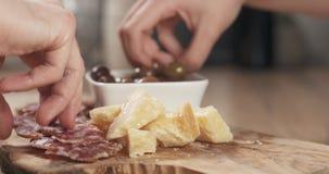 Χέρια που παίρνουν τα ιταλικά ορεκτικά antipasti από τον πίνακα Στοκ Εικόνες