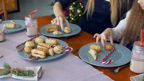 Χέρια που παίρνουν τα μπισκότα και την καραμέλα Χριστουγέννων από το πιάτο απόθεμα βίντεο