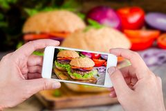 Χέρια που παίρνουν τα burgers φωτογραφιών με το smartphone Στοκ Εικόνα