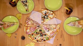 Χέρια που παίρνουν τις περικοπές πιτσών από το ξύλινο πιάτο στον πίνακα απόθεμα βίντεο