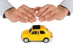 Χέρια που παρέχουν την προστασία πέρα από το κίτρινο αυτοκίνητο παιχνιδιών Στοκ Εικόνες