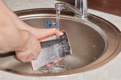 Χέρια που πλένουν και που καθαρίζουν τα ψάρια σολομών πέρα από το νεροχύτη κουζινών Στοκ Εικόνα