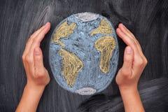 Χέρια που προστατεύουν το πλανήτη Γη στο μαύρο υπόβαθρο πινάκων κιμωλίας Στοκ Εικόνες