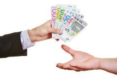 Χέρια που προσφέρουν τους ευρο- λογαριασμούς χρημάτων Στοκ Εικόνα