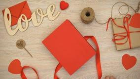 Χέρια που συσκευάζουν το κιβώτιο δώρων βαλεντίνων με τις καρδιά-διαμορφωμένες καραμέλες σοκολάτας, ρομαντικές φιλμ μικρού μήκους