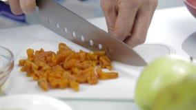 Χέρια που τεμαχίζουν τα ξηρά βερίκοκα με το μεγάλο μαχαίρι στον τέμνοντα πίνακα μαγειρεύοντας τρόφιμα υ&gamm φιλμ μικρού μήκους