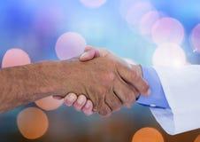 Χέρια που τινάζουν με το λαμπιρίζοντας ελαφρύ υπόβαθρο bokeh Στοκ Εικόνες