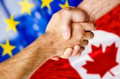 Χέρια που τινάζουν πέρα από τις καναδικές και ευρωπαϊκές σημαίες Στοκ εικόνα με δικαίωμα ελεύθερης χρήσης